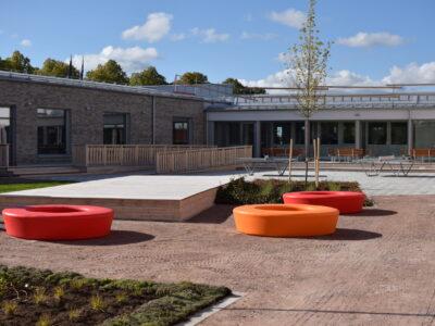 Tunboskolans landskapsarkitektur med färgglada element och aktiverande pingisbord