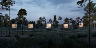 Framtidens semesterboenden i Svärdskolva med stora fönsterpartier som lyser upp i området i natten.