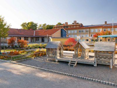 Blåsbo förskolas lekplats med lekstugor i trä