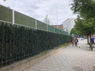 Staket och buskage som ramar in Ekens skola och skapar ett naturligt skydd ut mot gatan